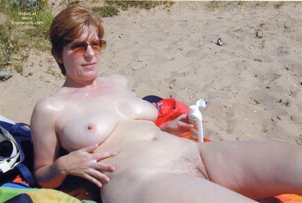 Обнаженные женщины и девушки нудисты лежат на пляже и загорают. . Пока они